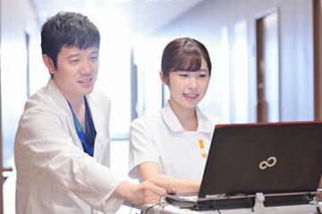 電子カルテを見ながら、医師に患者さんの対応について相談する。