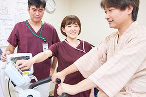 PTと一緒にリハビリ中の患者さんに声かけをする。リハビリに対する患者さんの意欲を引き出すためにも、声かけは大切。
