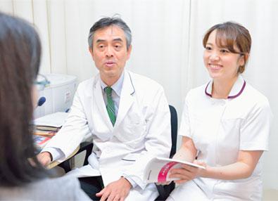 腹膜透析外来の医師とともに、患者さんがつけている「APD記録ノート」を見ながら質問に答える。